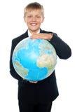 Gladlynt pojke i dräktholdingjordklot med båda händer Arkivbilder