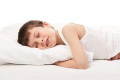 Gladlynt pojke i vit säng arkivfoto