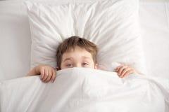 Gladlynt pojke i vit säng under den vita filten royaltyfria bilder