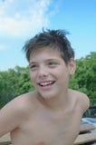 Gladlynt pojke på stranden arkivfoton