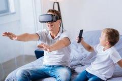 Gladlynt pojke som filmar hans fader som testar VR-hörlurar med mikrofon Royaltyfri Foto