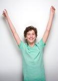 Gladlynt pojke som ler med lyftta händer Arkivbilder