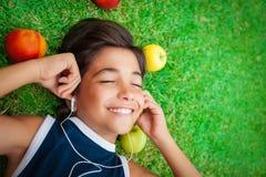 Gladlynt pojke som lyssnar till musik arkivbilder