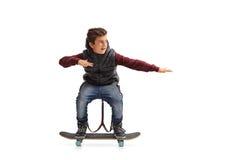 Gladlynt pojke som rider en skateboard Fotografering för Bildbyråer