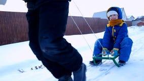 Gladlynt pojke som sledding i vintern lager videofilmer