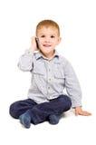 Gladlynt pojke som talar på telefonen Royaltyfria Bilder