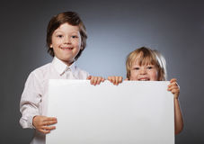 Gladlynt pojke som två rymmer ett baner Fotografering för Bildbyråer