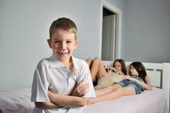 Gladlynt pojkeförgrund i rumwhithflickorna Royaltyfri Bild