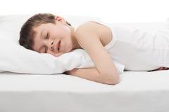 Gladlynt pojkesömn i säng Fotografering för Bildbyråer
