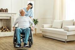 Gladlynt positiv anhörigvårdare som flyttar en rullstol Royaltyfri Fotografi