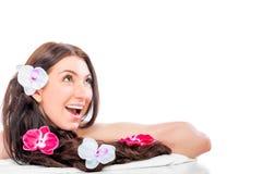 Gladlynt positiv flicka med orkidér i hennes hår Royaltyfri Fotografi