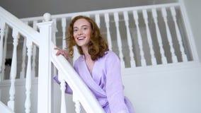 Gladlynt positiv flicka som poserar för kameran i ett purpurfärgat dräktanseende på en vit stege lager videofilmer