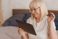 Gladlynt positiv kvinna som ser minnestavlaskärmen Arkivfoton