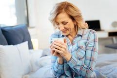 Gladlynt positiv vuxen kvinna som startar hennes dag med koppen av den varma drinken royaltyfri foto