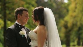 Gladlynt precis gift brud och brudgum som går att kyssa Det utomhus- skottet med sommar parkerar som bakgrund arkivfilmer