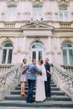 Gladlynt precis gift par med den lyckliga groomsmanen och brudtärnan som poserar på trappan av klassisk byggnad Royaltyfri Fotografi
