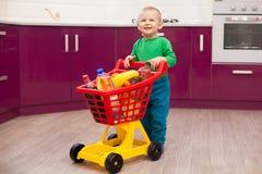 Gladlynt pys med shoppingvagnen Liten unge i spårvagn för barn för tillfälliga kläder bärande plast- shoppa Shopping rabatt, royaltyfri foto