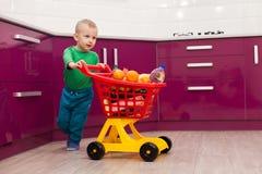 Gladlynt pys med shoppingvagnen Liten unge i spårvagn för barn för tillfälliga kläder bärande plast- shoppa Shopping rabatt, royaltyfria foton