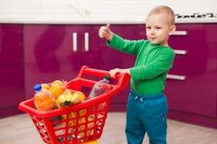 Gladlynt pys med shoppingvagnen Liten unge i spårvagn för barn för tillfälliga kläder bärande plast- shoppa Shopping rabatt, royaltyfri fotografi