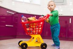 Gladlynt pys med shoppingvagnen Liten unge i spårvagn för barn för tillfälliga kläder bärande plast- shoppa Shopping rabatt, arkivfoto