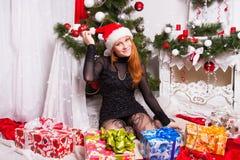 Gladlynt rödhårig flicka i den Santa Claus hatten Fotografering för Bildbyråer