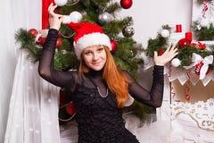 Gladlynt rödhårig flicka i den Santa Claus hatten Royaltyfria Bilder