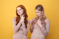 Gladlynt rödhårig mandam som trycker på hennes hår nära ledsen blond kvinna royaltyfri fotografi