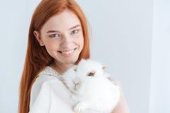 Gladlynt rödhårig mankvinna som poserar med kanin Arkivbild