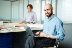Gladlynt rengöringsdukformgivare som använder bärbara datorn i öppet utrymmekontor royaltyfri foto