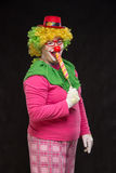 Gladlynt rolig clown i en hatt med en stor godis Arkivfoto