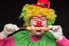 Gladlynt rolig clown i en hatt med en stor godis Fotografering för Bildbyråer