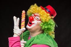 Gladlynt rolig clown i en hatt med en stor godis Royaltyfri Fotografi