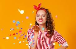 Gladlynt rolig ung kvinna med festliga konfettier på guling royaltyfri bild
