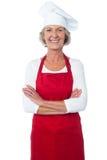 Gladlynt säker åldrig kvinnlig kock royaltyfri foto
