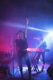 Gladlynt sångare som sjunger medan musiker som spelar pianot i upplyst nattklubb Arkivbilder