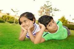 Gladlynt södra asiatisk pojke och flicka som ner ligger i en gräsmatta Royaltyfri Fotografi