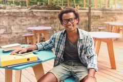Gladlynt sammanträde för ung man och le i utomhus- kafé royaltyfri foto
