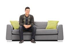 Gladlynt sammanträde för ung man på en modern soffa royaltyfria bilder