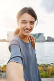Gladlynt selfie och le för ung kvinna talande Arkivbild