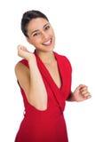 Gladlynt sexig brunett i rött göra en gest för klänning Royaltyfri Foto