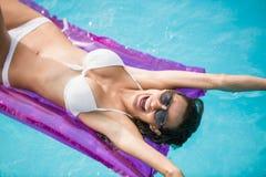 Gladlynt simning för ung kvinna med den uppblåsbara flotten royaltyfri fotografi