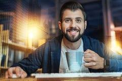 Gladlynt skäggig man som ler, medan dricka te på arbete Royaltyfri Foto