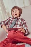 Gladlynt skolpojke som bär den rutiga skjortan med bandet som hemma kopplar av på en soffa med en minnestavladator royaltyfria bilder