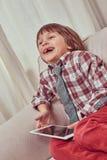 Gladlynt skolpojke som bär den rutiga skjortan med bandet som hemma kopplar av på en soffa med en minnestavladator royaltyfri bild