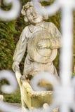 Gladlynt staty i trädgården - en pojke med skottkärran Royaltyfria Bilder