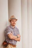 Gladlynt stilfull grabb i hattbenägenhet på väggen utomhus Royaltyfri Foto