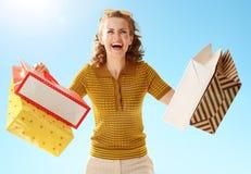 Gladlynt stilfull kvinna med shoppingpåsar mot blå himmel royaltyfri fotografi
