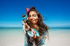 Gladlynt stilfull ung kvinna i grov bomullstvillomslag på stranden royaltyfri fotografi
