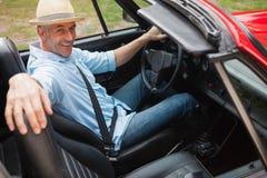 Gladlynt stilig man som poserar i röd cabriolet royaltyfri fotografi