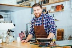 Gladlynt stilig ung barista med skägget som arbetar i coffee shop Royaltyfri Bild